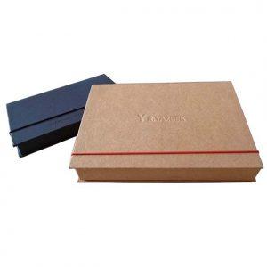 22 caixa tipo book, revestimento papel kraft, fechamento com elástico e aplicação de logo em baixo relevo
