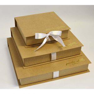 23 caixa tipo book, revestimento em papel kraft, personalização em couro sitético dourado.